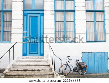 A bicycle parked near the facade of white building with blue colored windows and door. - stock photo