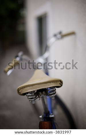 a bicycle sits against the wall in the summer time with the focus on the seat in the foreground - stock photo
