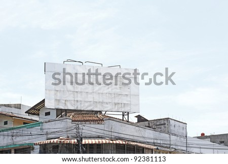 A big blank grungy metallic advertisement board with space for text, on the rooftop of an old aging vintage shop house against a clear blue sky. - stock photo