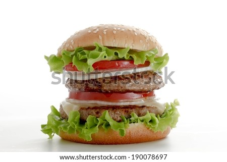 A big burger with meat, lettuce ,tomatoes and onions. - stock photo