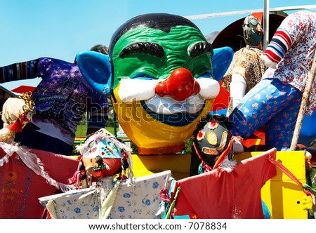 A big clown face in the middle of a bunch of scarecrows. - stock photo