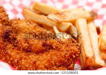 a big diner style plate of breaded chicken tenders and hand cut french fries - stock photo