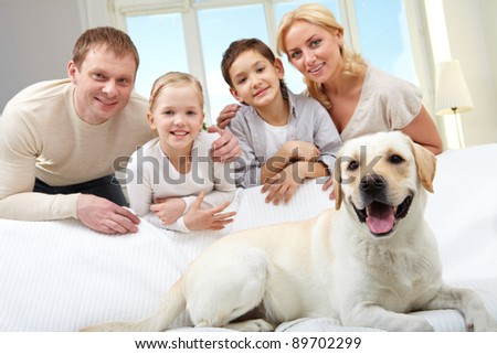 A big dog lying on sofa, a family of four standing behind - stock photo