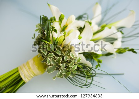 A big flower bouquet filled with cala lillies and other plants. - stock photo