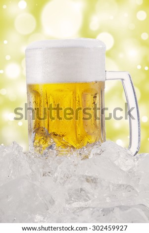 A big glass full of fresh beer with froth and ice cube, shot with bokeh background - stock photo