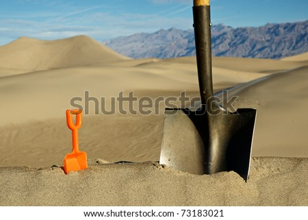 A big shovel and little shovel pair off to decide who should begin the massive earth-moving project. - stock photo
