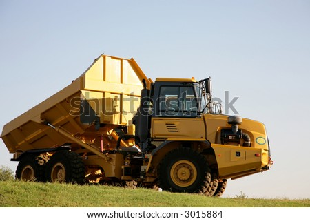 A big yellow truck standing outside - stock photo