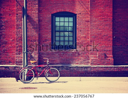 a bike in front of a brick wall during summer toned with a retro vintage instagram filter effect - stock photo