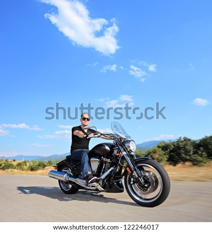 A biker riding a customized motorcycle on an open road, shot with a tilt and shift lens - stock photo