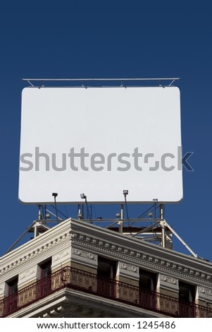 A billboard mounted on the roof of a corner building. - stock photo