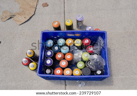 A Bin of Spray Paint Bottles on the Sidewalk - stock photo