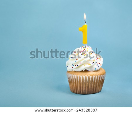 A birthday cup cake with buttercream icing,  sprinkles and a lit number one birthday candle. - stock photo