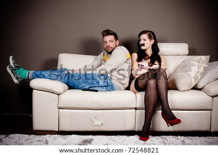 A bizarre living room scene. A woman in lingerie with her mouth taped and a hunched weird man on the couch. High contrast and vignette added. - stock photo