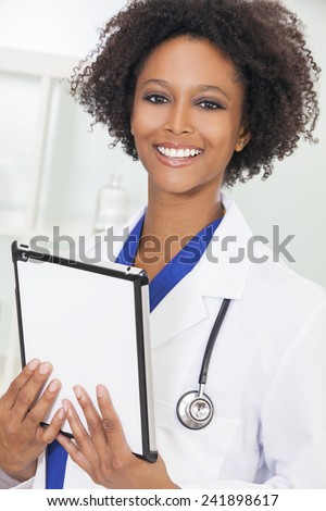 A black African American female medical doctor using a tablet computer in a hospital  - stock photo
