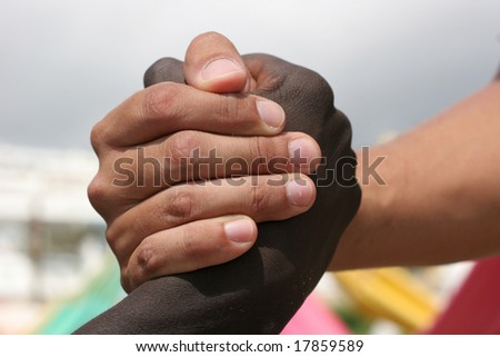 A black and a white person shake hands - stock photo
