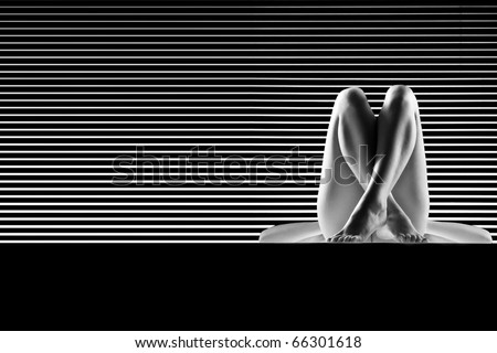 a black and white artistic nude of a woman, shot on striped background. she is sitting down on her back, with both her knees up and crossed. - stock photo