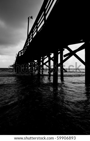 A black and white image of a fishing pier going off into the distance - stock photo
