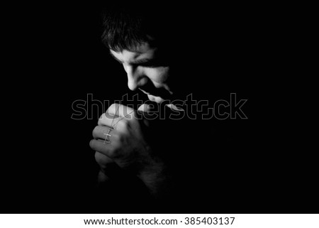 A black and white image of a man kneeling down praying to God. - stock photo