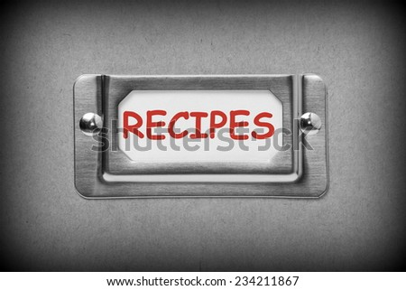 A black and white image of a metal drawer label holder with a white card and the title Recipes added in red text - stock photo