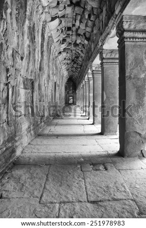 a black and white image of a reconstructed hallway which is part of ancient Khmer ruins of Cambodia - stock photo