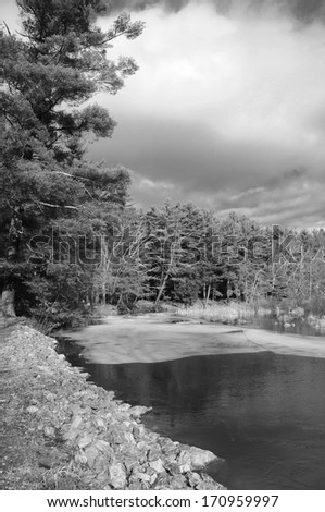 A black and white image of ice on the Bantam River flowing through White Memorial located in Litchfield Connecticut on a sunny winter day.  - stock photo