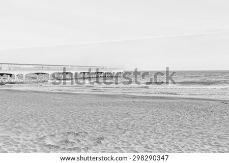 A black and white image of sunset light, of a pier looking towards the sea at the beach with sand  and one strip of dramatic clouds on a slight angle, in the  in Europe. A high key filter applied. - stock photo