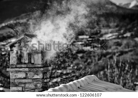 A black and white mountain house roof with smoking chimney - stock photo