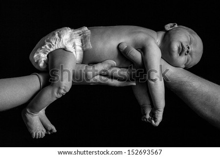A black and white shot of a newborn baby boy being held up by two hands. - stock photo