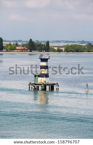 A black and white striped, solar powered channel marker in a canal near Venice - stock photo