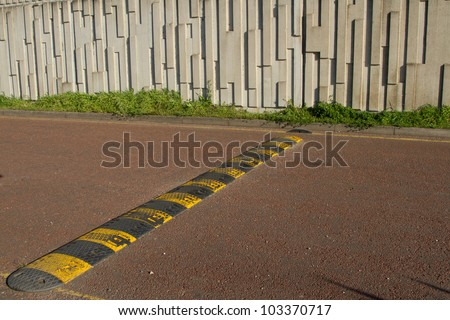 A black and yellow speed bump, rumble strip stretches across a red tarmac road. - stock photo