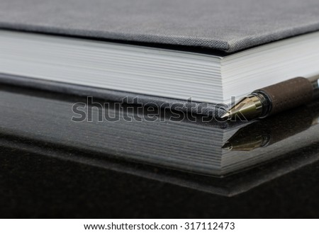 A black ball point and hard cover  note  book on black polish granite top with reflection. - stock photo