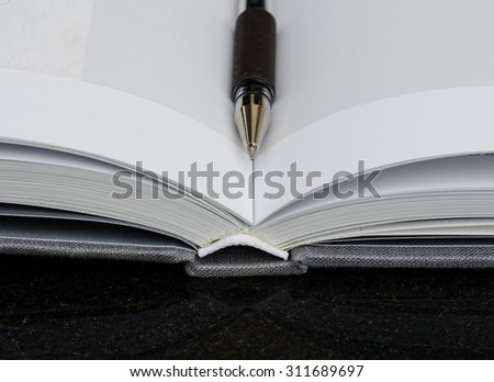 A black ball point pen marked on open note book on black polish granite top with reflection. - stock photo
