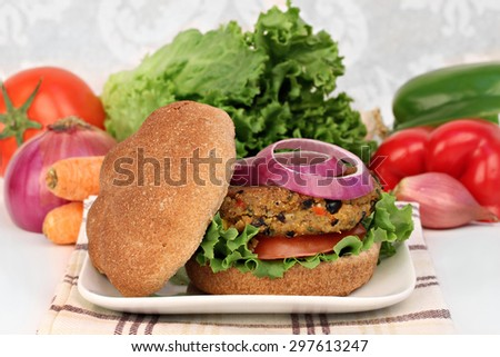 A black bean vegetarian burger on a whole wheat roll with tomato, onion and greens. - stock photo