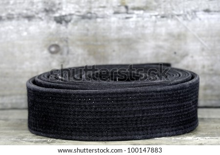 a black belt on wooden background - stock photo