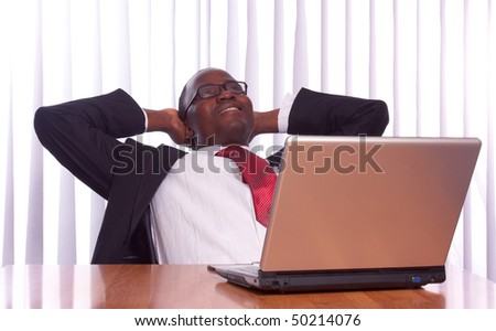 A black businessman working at his desk on a laptop - stock photo