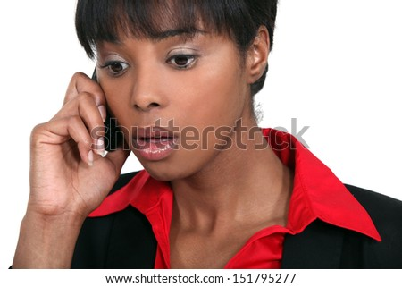 A black businesswoman getting bad news on the phone. - stock photo