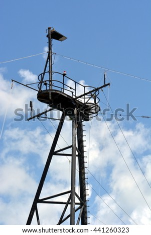 A black crow's nest tower on a ship against blue sky with clouds, - stock photo