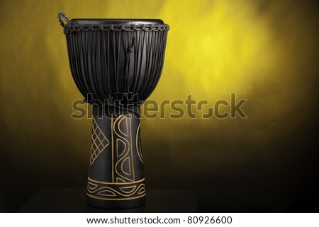 A black djembe conga drum isolated against a yellow spotlight background. - stock photo