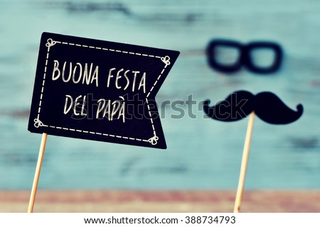 a black flag-shaped signboard with the text buona festa del papa, happy fathers day in italian, and a mustache and a pair of eyeglasses forming the face of a man, against a blue wooden background - stock photo