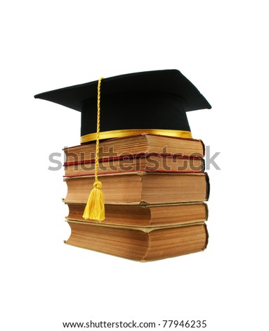 A black graduation cap on top of a stack of old books isolated on a white background - stock photo