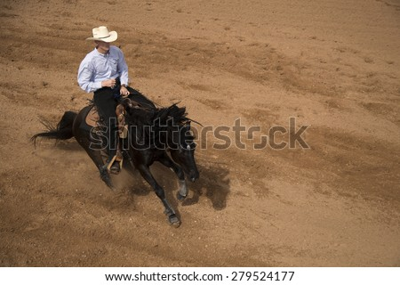 A black horse with his trainer cowboy riding and training him. - stock photo