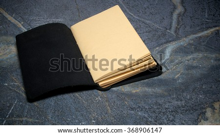 A black leather bound book is open to the first page that is blank on soapstone table top. - stock photo