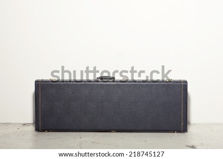 A black leather guitar case at grunge bottom  - stock photo
