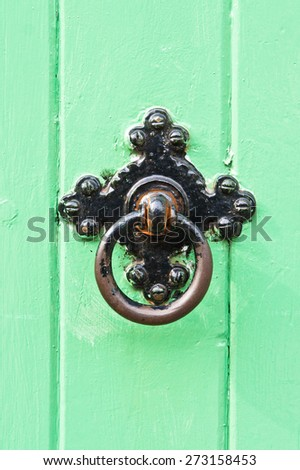 A black metal knowcker on a green wooden door - stock photo