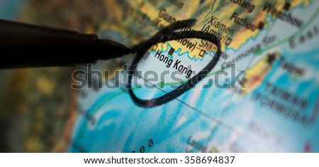 A black pen circles the world's most vertically developed city, Hong Kong Special Administrative Region of the People's Republic of China, to highlight it as a point of interest on a globe. - stock photo