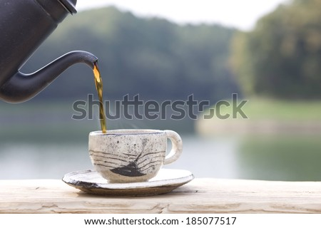 A black pot pouring into a cup on a ledge overlooking a lake. - stock photo