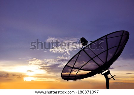 A black satellite dish on twilight sky background - stock photo