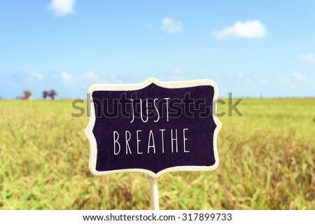 a black signboard with the text just breathe written in it in a peaceful landscape - stock photo