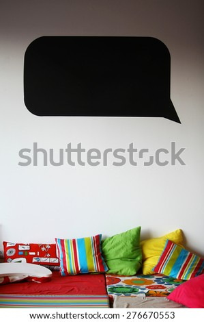 A black speech bubble on a wall above a bed. - stock photo