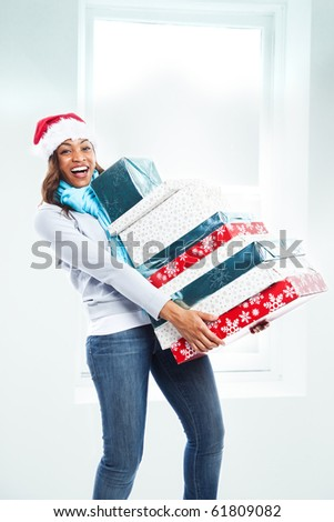 A black woman celebrating christmas carrying gift boxes - stock photo
